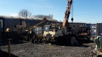 Rotting and rusting crane lorry, train carriages and other equipment